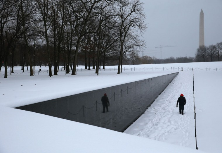 A man walks along the snow-covered Vietnam Memorial in Washington, DC. (Photo by Mark Wilson/Getty Images)