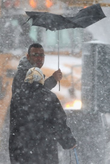 A man holds an upturned umbrella during a snowstorm in New York City. (Photo by John Moore/Getty Images)