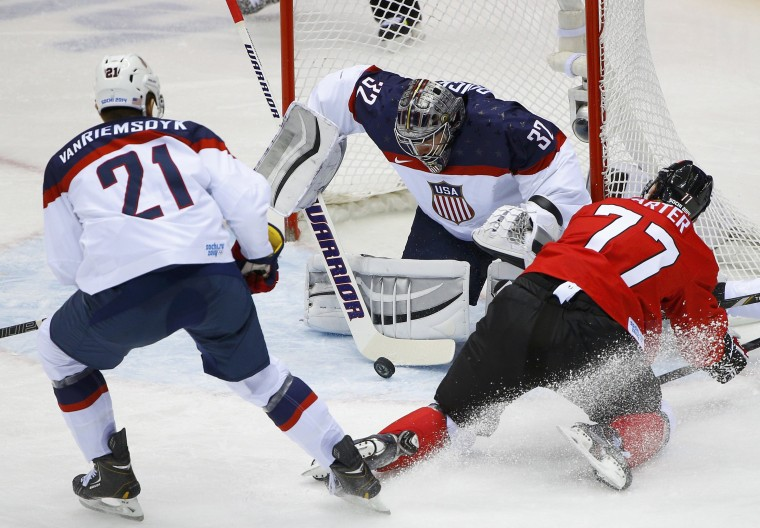 Team USA's goalie Jonathan Quick makes a save between Team USA's James van Riemsdyk (L) and Canada's Jeff Carter during the first period of the men's ice hockey semi-final game at the 2014 Sochi Winter Olympic Games, February 21, 2014. (REUTERS/Brian Snyder)