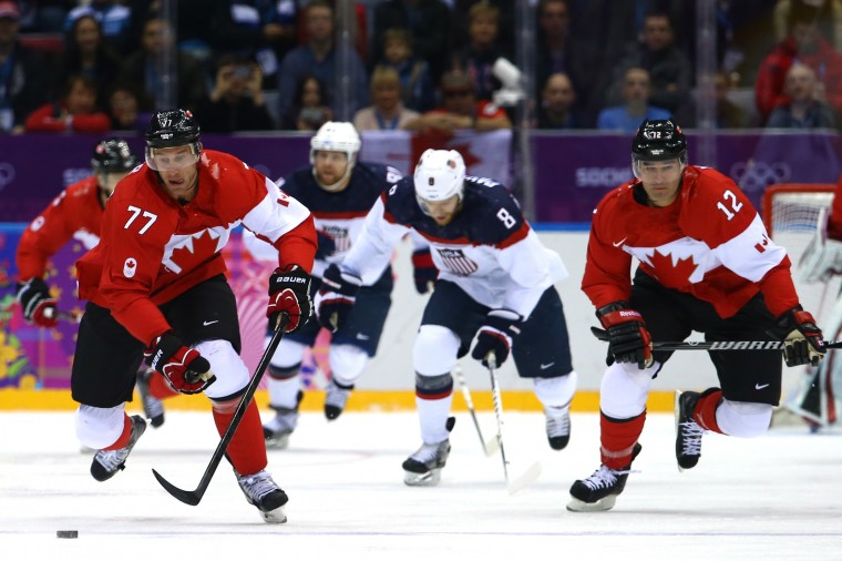 Jeff Carter #77 of Canada controls the puck as Joe Pavelski #8 of the United States follows during the Men's Ice Hockey Semifinal Playoff on Day 14 of the 2014 Sochi Winter Olympics at Bolshoy Ice Dome on February 21, 2014 in Sochi, Russia. (Photo by Al Bello/Getty Images)