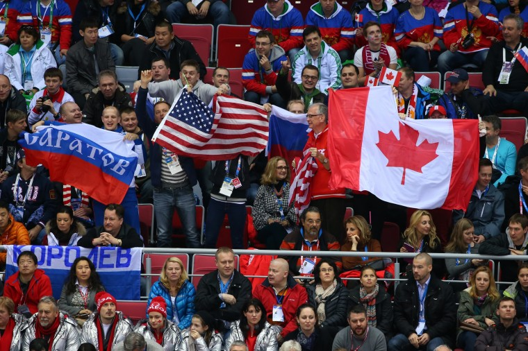 Fans wave flags during the Men's Ice Hockey Semifinal Playoff between Canada and the United States on Day 14 of the 2014 Sochi Winter Olympics at Bolshoy Ice Dome on February 21, 2014 in Sochi, Russia. (Photo by Julian Finney/Getty Images)