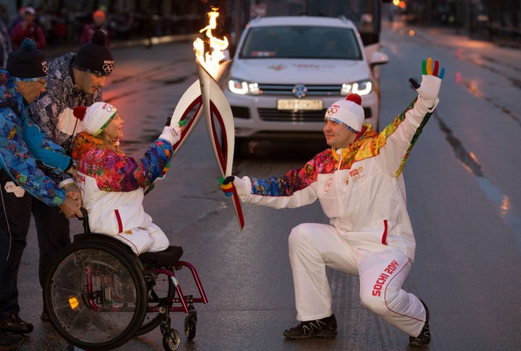 A handout picture taken during the Sochi 2014 Winter Olympic torch relay on November 2, 2013, and released by the Sochi 2014 Winter Olympics Organizing Committee shows torchbearers, Maria Iovleva (L), a Russian biathlete and cross-country skier representing Russia at the 2010 Winter Paralympics, and Ivan Volzhanin (R) 'kissing' with their torches to pass the Olympic flame in Syktyvkar, 1300 km (812 miles) north-east of Moscow. Russian torchbearers has started in October the history's longest Olympic torch relay ahead of Winter Games in Sochi, which will take the flame across the country through all 83 of its regions, including extreme locales such as Chukotka, the remote region in Russia's Far East, the turbulent North Caucasus, and even Russia's European exclave Kaliningrad. (Sochi/Getty Images)