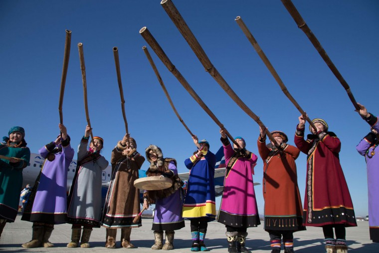 A handout picture taken during the Sochi 2014 Winter Olympic torch relay on November 14, 2013, and released by the Sochi 2014 Winter Olympics Organizing Committee shows musicians of Nivkh indigenous ethnic group wearing their traditional costumes and rising Kalni musical pipes during welcome ceremony for the Olympic flame in Yuzhno-Sakhalinsk airport on the Russia'sPacific Island of Sakhalin 7309 km (4542 miles) east of Moscow. Russian torchbearers has started in October the history's longest Olympic torch relay ahead of Winter Games in Sochi, which will take the flame across the country through all 83 of its regions, including extreme locales such as Chukotka, the remote region in Russia's Far East, the turbulent North Caucasus, and even Russia's European exclave Kaliningrad. (Sochi 2014/Getty Images)