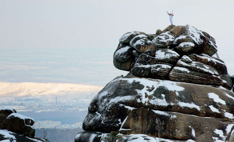 A handout picture taken during the Sochi 2014 Winter Olympic torch relay on November 26, 2013, and released by the Sochi 2014 Winter Olympics Organizing Committee shows Russian mountain-climber Vladimir Gunko rising an Olympic torch while standing atop of a rock at the Stolby (Pillars) national nature reserve in the Siberian Krasnoyarsk region, some 3500 km (2174 miles) east of Moscow. Russian torchbearers has started in October the history's longest Olympic torch relay ahead of Winter Games in Sochi, which will take the flame across the country through all 83 of its regions, including extreme locales such as Chukotka, the remote region in Russia's Far East, the turbulent North Caucasus, and even Russia's European exclave Kaliningrad. (Sochi 2014/Getty Images)