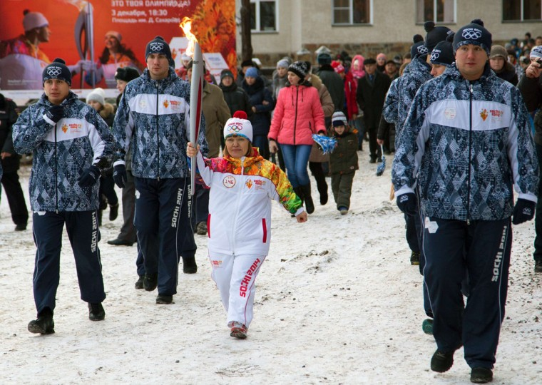 A handout picture taken during the Sochi 2014 Winter Olympic torch relay on December 3, 2013, and released by the Sochi 2014 Winter Olympics Organizing Committee shows a torchbearer carrying an Olympic torch in Russia's Siberian city of Barnaul 3400 km (2012 miles) southeast of Moscow. Russian torchbearers has started in October the history's longest Olympic torch relay ahead of Winter Games in Sochi, which will take the flame across the country through all 83 of its regions, including extreme locales such as Chukotka, the remote region in Russia's Far East, the turbulent North Caucasus, and even Russia's European exclave Kaliningrad. (Sochi 2014/Getty Images)