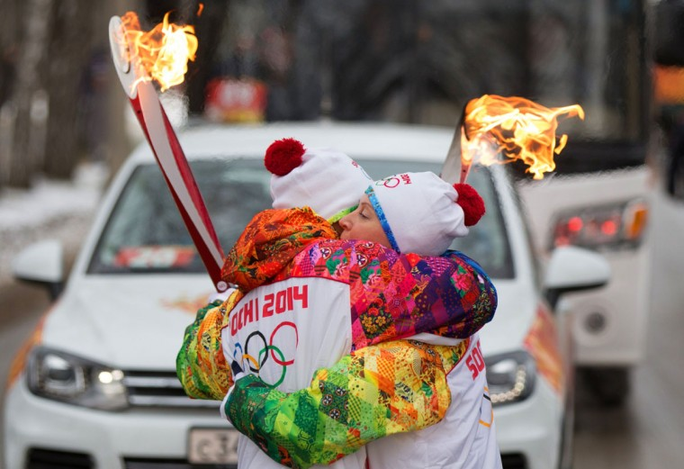 A handout picture taken during the Sochi 2014 Winter Olympic torch relay on December 7, 2013, and released by the Sochi 2014 Winter Olympics Organizing Committee shows torchbearers hugging each other in Russia's Siberian city of Novosibirsk, about 2800 km (1750 miles) east of Moscow. Russian torchbearers has started in October the history's longest Olympic torch relay ahead of Winter Games in Sochi, which will take the flame across the country through all 83 of its regions, including extreme locales such as Chukotka, the remote region in Russia's Far East, the turbulent North Caucasus, and even Russia's European exclave Kaliningrad. (Sochi 2014/Getty Images)