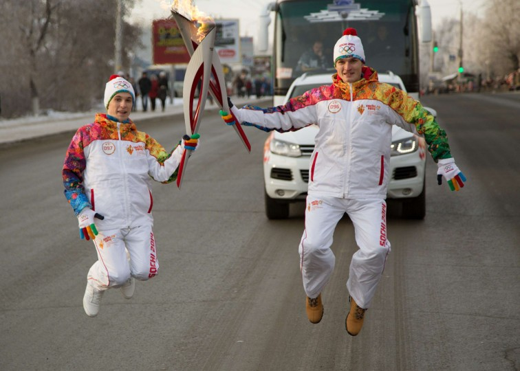 A handout picture taken during the Sochi 2014 Winter Olympic torch relay on December 9, 2013, and released by the Sochi 2014 Winter Olympics Organizing Committee shows torchbearers jumping in Russia's Siberian city of Omsk, 2243 km (1394 miles) of Moscow. Russian torchbearers has started in October the history's longest Olympic torch relay ahead of Winter Games in Sochi, which will take the flame across the country through all 83 of its regions, including extreme locales such as Chukotka, the remote region in Russia's Far East, the turbulent North Caucasus, and even Russia's European exclave Kaliningrad. (Sochi 2014/Getty Images)