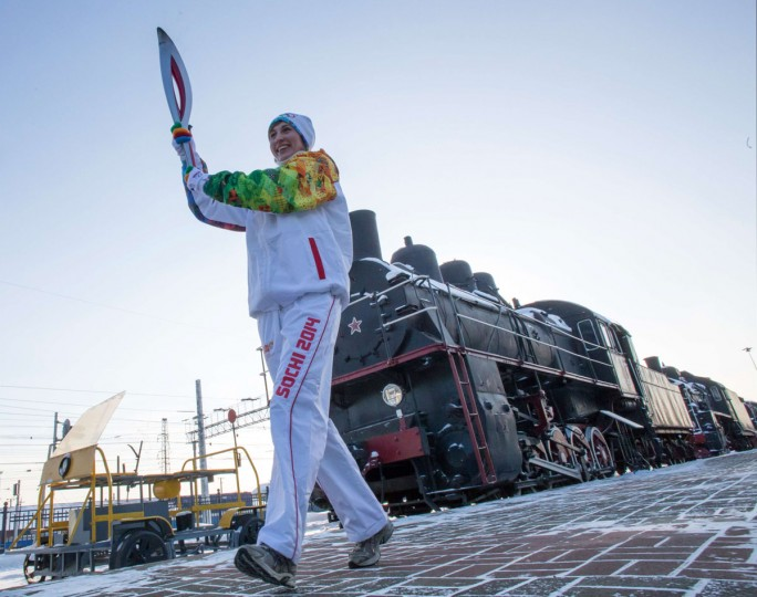 A handout picture taken during the Sochi 2014 Winter Olympic torch relay on December 16, 2013, and released by the Sochi 2014 Winter Olympics Organizing Committee shows a torchbearer carrying an Olympic torch at a Railway Museum in Russia's Urals city of Chelyabinsk, 1500 km (932 miles) east of Moscow. Russian torchbearers has started in October the history's longest Olympic torch relay ahead of Winter Games in Sochi, which will take the flame across the country through all 83 of its regions, including extreme locales such as Chukotka, the remote region in Russia's Far East, the turbulent North Caucasus, and even Russia's European exclave Kaliningrad. (Sochi 2014/Getty Images)
