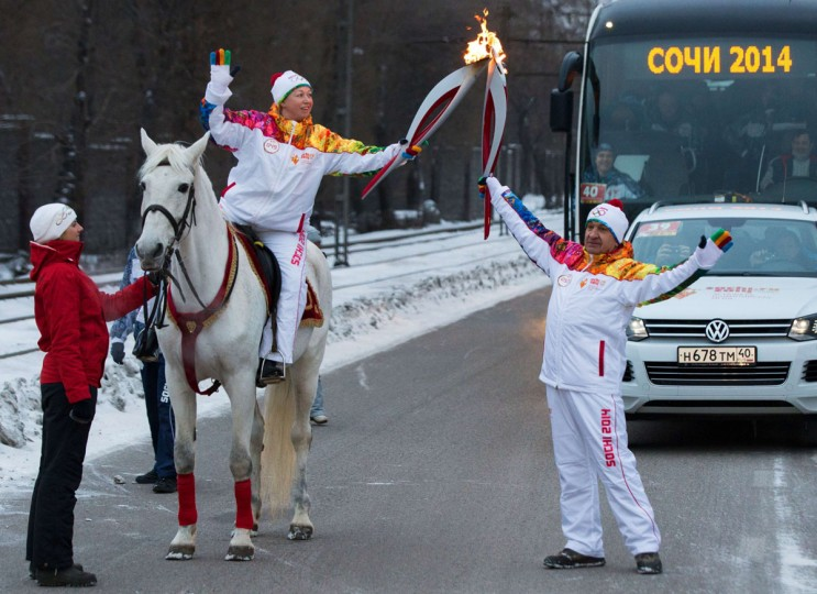 A handout picture taken during the Sochi 2014 Winter Olympic torch relay on December 18, 2013, and released by the Sochi 2014 Winter Olympics Organizing Committee shows torchbearers 'kissing' with their torches to pass the Olympic flame in Russia's Urals city of Chelyabinsk, 1500 km (932 miles) east of Moscow. Russian torchbearers has started in October the history's longest Olympic torch relay ahead of Winter Games in Sochi, which will take the flame across the country through all 83 of its regions, including extreme locales such as Chukotka, the remote region in Russia's Far East, the turbulent North Caucasus, and even Russia's European exclave Kaliningrad. (Sochi 2014/Getty Images)