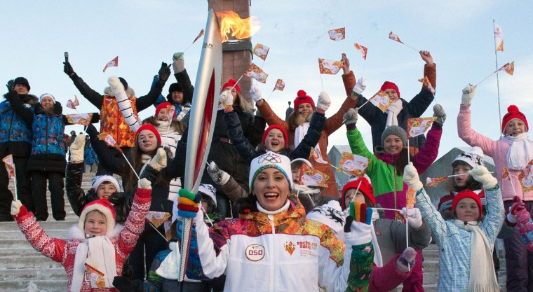 A handout picture taken during the Sochi 2014 Winter Olympic torch relay on December 21, 2013, and released by the Sochi 2014 Winter Olympics Organizing Committee shows torchbearer posing for a photo with children in Ufa, the regional capital of the Volga River region of Bashkortostan, about 1200 kilometers (750 miles) east of Moscow. Russian torchbearers has started in October the history's longest Olympic torch relay ahead of Winter Games in Sochi, which will take the flame across the country through all 83 of its regions, including extreme locales such as Chukotka, the remote region in Russia's Far East, the turbulent North Caucasus, and even Russia's European exclave Kaliningrad. (Sochi 2014/Getty Images)