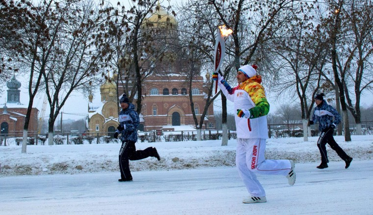 A handout picture taken during the Sochi 2014 Winter Olympic torch relay on December 22, 2013, and released by the Sochi 2014 Winter Olympics Organizing Committee shows a torchbearer carrying an Olympic torch in the city of Orenburg, about 1300 kilometers (800 miles) southeast of Moscow. Russian torchbearers has started in October the history's longest Olympic torch relay ahead of Winter Games in Sochi, which will take the flame across the country through all 83 of its regions, including extreme locales such as Chukotka, the remote region in Russia's Far East, the turbulent North Caucasus, and even Russia's European exclave Kaliningrad. (Sochi 2014/Getty Images)