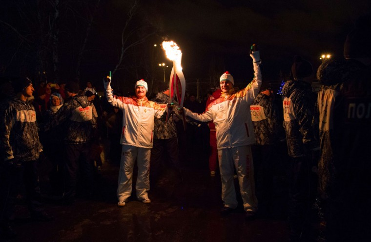 A handout picture taken during the Sochi 2014 Winter Olympic torch relay on December 24, 2013, and released by the Sochi 2014 Winter Olympics Organizing Committee shows torchbearers, Russian World gymnastic champion Alexey Nemov (L), and footballer Sergey Efimov (R) 'kissing' with their torches to pass the Olympic flame in in the Volga River city of Togliatti, some 800 km (497 miles) southeast of Moscow. Russian torchbearers has started in October the history's longest Olympic torch relay ahead of Winter Games in Sochi, which will take the flame across the country through all 83 of its regions, including extreme locales such as Chukotka, the remote region in Russia's Far East, the turbulent North Caucasus, and even Russia's European exclave Kaliningrad. (Sochi 2014/Getty Images)