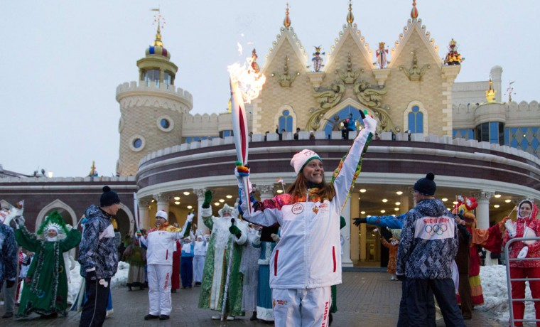 A handout picture taken during the Sochi 2014 Winter Olympic torch relay on December 31, 2013, and released by the Sochi 2014 Winter Olympics Organizing Committee showsa torchbearer carrying an Olympic torch in the Volga River city of Kazan, some 720 km (450 miles) east of Moscow. Russian torchbearers has started in October 2013 the history's longest Olympic torch relay ahead of February's Winter Games in Sochi, which will take the flame across the country through all 83 of its regions, including extreme locales such as Chukotka, the remote region in Russia's Far East, the turbulent North Caucasus, and even Russia's European exclave Kaliningrad. (Sochi 2014/Getty Images)