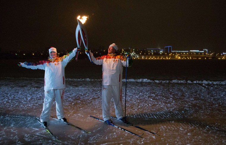 A handout picture taken during the Sochi 2014 Winter Olympic torch relay on January 2, 2014, and released by the Sochi 2014 Winter Olympics Organizing Committee shows torchbearers 'kissing' with their torches to pass the Olympic flame in Izhevsk, some 1000 km (625 miles) east of Moscow. Russian torchbearers has started in October 2013 the history's longest Olympic torch relay ahead of February's Winter Games in Sochi, which will take the flame across the country through all 83 of its regions, including extreme locales such as Chukotka, the remote region in Russia's Far East, the turbulent North Caucasus, and even Russia's European exclave Kaliningrad. (Sochi 2014/Getty Images)