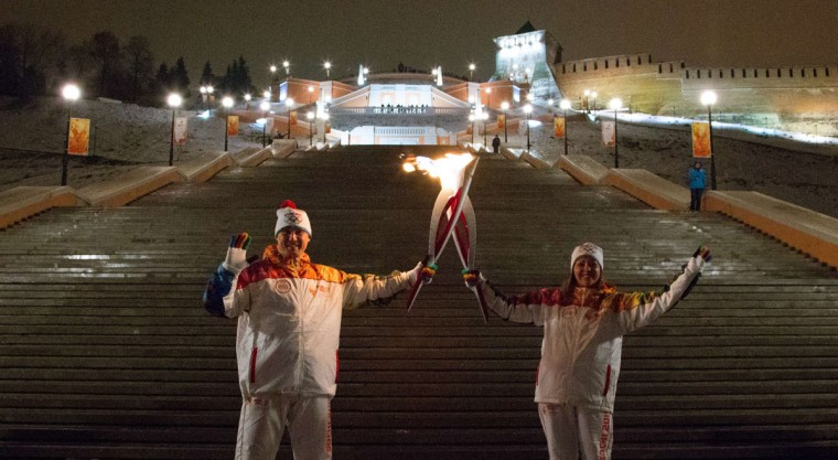 A handout picture taken during the Sochi 2014 Winter Olympic torch relay on January 8, 2014, and released by the Sochi 2014 Winter Olympics Organizing Committee shows torchbearers 'kissing' with their torches to pass the Olympic flame in in the Volga River city of Nizhniy Novgorod, 440 km (250 miles) east of Moscow. Russian torchbearers has started in October the history's longest Olympic torch relay ahead of Winter Games in Sochi, which will take the flame across the country through all 83 of its regions, including extreme locales such as Chukotka, the remote region in Russia's Far East, the turbulent North Caucasus, and even Russia's European exclave Kaliningrad. (Sochi 2014/Getty Images)