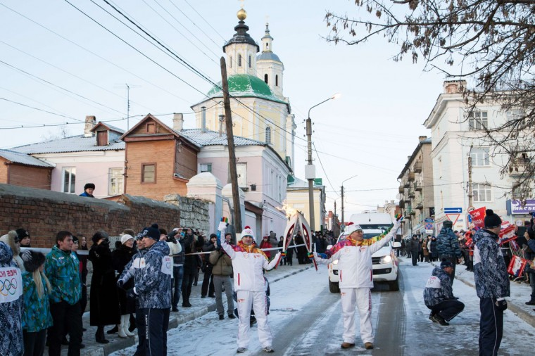 A handout picture taken during the Sochi 2014 Winter Olympic torch relay on January 14, 2014, and released by the Sochi 2014 Winter Olympics Organizing Committee shows torchbearers 'kissing' with their torches to pass the Olympic flame in the ancient Russian city of Yelets, some 380 km (237 miles) south of Moscow. Russian torchbearers has started in October the history's longest Olympic torch relay ahead of Winter Games in Sochi, which will take the flame across the country through all 83 of its regions, including extreme locales such as Chukotka, the remote region in Russia's Far East, the turbulent North Caucasus, and even Russia's European exclave Kaliningrad. (Sochi 2014/Getty Images)
