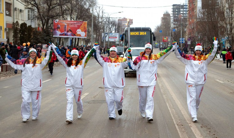 A handout picture taken during the Sochi 2014 Winter Olympic torch relay on January 22, 2014, and released by the Sochi 2014 Winter Olympics Organizing Committee shows torchbearers carrying an Olympic torch in the city of Rostov-on-Don, some 1,000 km (600 miles) south of Moscow. Russian torchbearers has started in October 2013 the history's longest Olympic torch relay ahead of Winter Games in Sochi, which will take the flame across the country through all 83 of its regions, including extreme locales such as Chukotka, the remote region in Russia's Far East, the turbulent North Caucasus, and even Russia's European exclave Kaliningrad. (Sochi 2014/Getty Images)