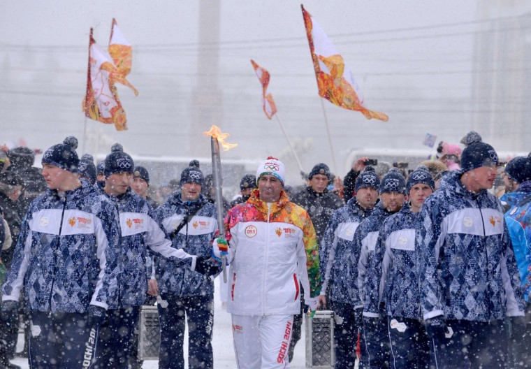 A torchbearer carries an Olympic torch during the Sochi 2014 Winter Olympic torch relay in the southern Russian city of Stavropol, on January 23, 2014. Russian torchbearers has started in October 2013 the history's longest Olympic torch relay ahead of Winter Games in Sochi, which will take the flame across the country through all 83 of its regions, including extreme locales such as Chukotka, the remote region in Russia's Far East, the turbulent North Caucasus, and even Russia's European exclave Kaliningrad. (Danil Semyonov/AFP/Getty Images)