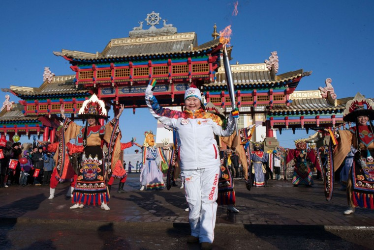 A handout picture taken during the Sochi 2014 Winter Olympic torch relay on January 25, 2014 and released by the Sochi 2014 Winter Olympics Organizing Committee, shows a torchbearer carrying an Olympic torch in front of a Buddhist shrine in Elista, the capital of Kalmykia region, some 1600 km (1000 miles) southeast of Moscow. Russian torchbearers has started in October 2013 the history's longest Olympic torch relay ahead of February's Winter Games in Sochi, which will take the flame across the country through all 83 of its regions, including extreme locales such as Chukotka, the remote region in Russia's Far East, the turbulent North Caucasus, and even Russia's European exclave Kaliningrad. (Sochi 2014/Getty Images)
