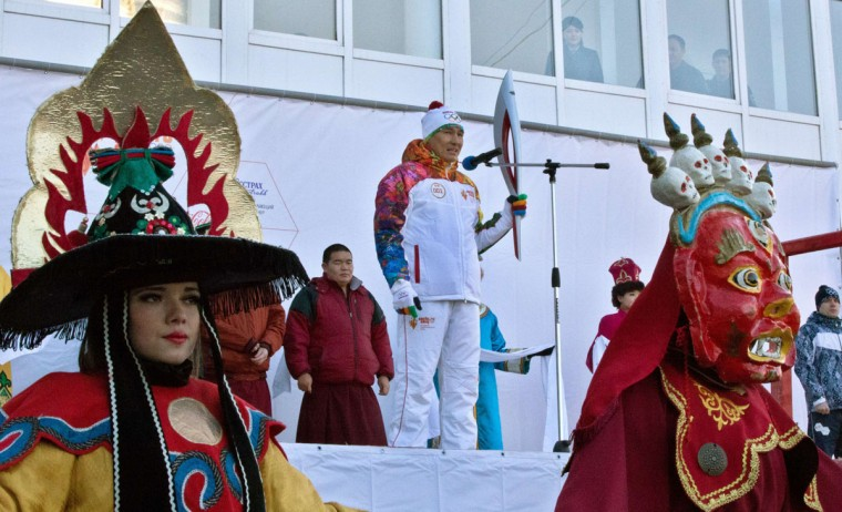 A handout picture taken during the Sochi 2014 Winter Olympic torch relay on January 25, 2014 and released by the Sochi 2014 Winter Olympics Organizing Committee, shows a torchbearer holding an Olympic torch during a welcome ceremony in Elista, the capital of Kalmykia region, some 1600 km (1000 miles) southeast of Moscow. Russian torchbearers has started in October 2013 the history's longest Olympic torch relay ahead of February's Winter Games in Sochi, which will take the flame across the country through all 83 of its regions, including extreme locales such as Chukotka, the remote region in Russia's Far East, the turbulent North Caucasus, and even Russia's European exclave Kaliningrad. (Sochi 2014/Getty Images)
