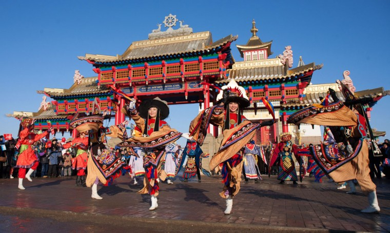 A handout picture taken during the Sochi 2014 Winter Olympic torch relay on January 25, 2014 and released by the Sochi 2014 Winter Olympics Organizing Committee, shows Kalmyk dancers performing to welcome the Olympic flame arrival in front of a Buddhist shrine in Elista, the capital of Kalmykia region, some 1600 km (1000 miles) southeast of Moscow. Russian torchbearers has started in October 2013 the history's longest Olympic torch relay ahead of February's Winter Games in Sochi, which will take the flame across the country through all 83 of its regions, including extreme locales such as Chukotka, the remote region in Russia's Far East, the turbulent North Caucasus, and even Russia's European exclave Kaliningrad. (Sochi 2014/Getty Images)
