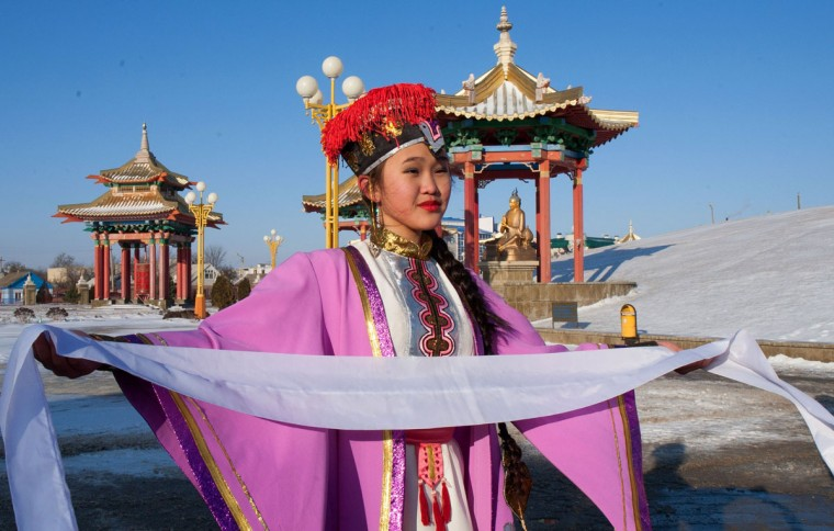 A handout picture taken during the Sochi 2014 Winter Olympic torch relay on January 25, 2014 and released by the Sochi 2014 Winter Olympics Organizing Committee, shows Kalmyk girl wearing traditional costume during a ceremony to mark the Olympic flame arrival in front of a Buddhist shrine in Elista, the capital of Kalmykia region, some 1600 km (1000 miles) southeast of Moscow. Russian torchbearers has started in October 2013 the history's longest Olympic torch relay ahead of February's Winter Games in Sochi, which will take the flame across the country through all 83 of its regions, including extreme locales such as Chukotka, the remote region in Russia's Far East, the turbulent North Caucasus, and even Russia's European exclave Kaliningrad. (Sochi 2014/Getty Images)