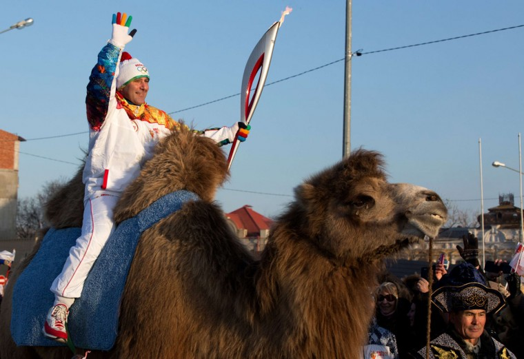 A handout picture taken during the Sochi 2014 Winter Olympic torch relay on January 26, 2014, and released by the Sochi 2014 Winter Olympics Organizing Committee shows a torchbearer riding a camel in the Russian Caspian Sea port of Astrakhan. Russian torchbearers has started in October 2013 the history's longest Olympic torch relay ahead of Winter Games in Sochi, which will take the flame across the country through all 83 of its regions, including extreme locales such as Chukotka, the remote region in Russia's Far East, the turbulent North Caucasus, and even Russia's European exclave Kaliningrad. (Sochi 2014/Getty Images)