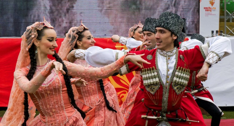 A handout picture taken during the Sochi 2014 Winter Olympic torch relay on January 27, 2014, and released by the Sochi 2014 Winter Olympics Organizing Committee shows dancers wearing traditional costumes of the North Caucasus ethnic groups while performing at a stadium, the site of the torch relay, in Makhachkala, the capital of Russia's troubled southern republic of Dagestan. Russian torchbearers has started in October 2013 the history's longest Olympic torch relay ahead of Winter Games in Sochi, which will take the flame across the country through all 83 of its regions, including extreme locales such as Chukotka, the remote region in Russia's Far East, the turbulent North Caucasus, and even Russia's European exclave Kaliningrad. (Sochi 2014/Getty Images)