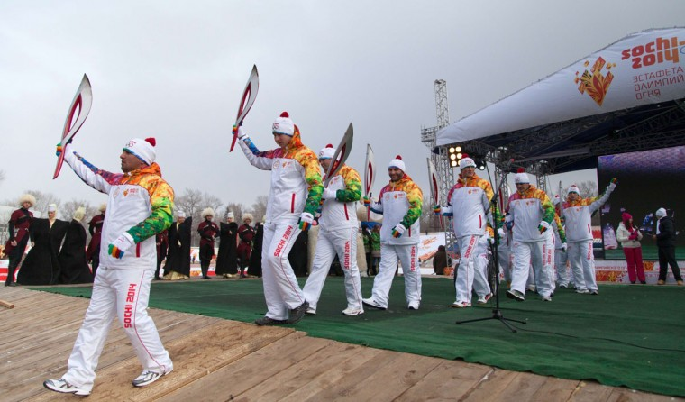 A handout picture taken during the Sochi 2014 Winter Olympic torch relay on January 27, 2014, and released by the Sochi 2014 Winter Olympics Organizing Committee shows torchbearers walking past actors wearing traditional costumes of the North Caucasus ethnic groups at the site of the torch relay in Cherkessk, the capital of Russia's southern Karachay-Cherkess republic. Russian torchbearers has started in October 2013 the history's longest Olympic torch relay ahead of Winter Games in Sochi, which will take the flame across the country through all 83 of its regions, including extreme locales such as Chukotka, the remote region in Russia's Far East, the turbulent North Caucasus, and even Russia's European exclave Kaliningrad. (Sochi 2014/Getty Images)
