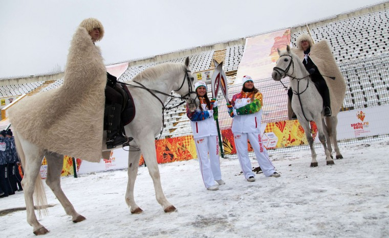 A handout picture taken during the Sochi 2014 Winter Olympic torch relay on January 30, 2014 and released by the Sochi 2014 Winter Olympics Organizing Committee, shows torchbearers 'kissing' with their torches to pass the Olympic flame in the company of horsemen wearing traditional costumes in Vladikavkaz, the capital of Russia's North Caucasus region of North Ossettia. Russian torchbearers has started in October 2013 the history's longest Olympic torch relay ahead of February's Winter Games in Sochi, which will take the flame across the country through all 83 of its regions, including extreme locales such as Chukotka, the remote region in Russia's Far East, the turbulent North Caucasus, and even Russia's European exclave Kaliningrad. (Sochi 2014/Getty Images)