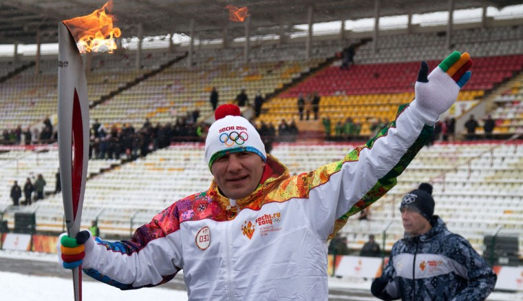 A handout picture taken during the Sochi 2014 Winter relay on January 30, 2014 and released by the Sochi 2014 Winter Olympics Organizing Committee, shows a torchbearer carrying an Olympic torch at a stadium in Vladikavkaz, the capital of Russia's North Caucasus region of North Ossettia. Russian torchbearers has started in October 2013 the history's longest Olympic torch relay ahead of February's Winter Games in Sochi, which will take the flame across the country through all 83 of its regions, including extreme locales such as Chukotka, the remote region in Russia's Far East, the turbulent North Caucasus, and even Russia's European exclave Kaliningrad. (Sochi 2014/Getty Images)