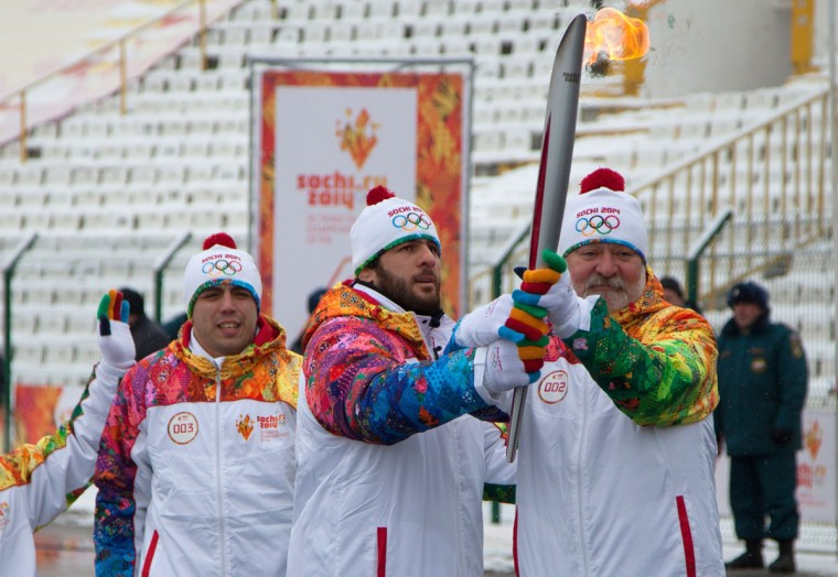 A handout picture taken during the Sochi 2014 Winter relay on January 30, 2014 and released by the Sochi 2014 Winter Olympics Organizing Committee, shows torchbearers carrying an Olympic torch at a stadium in Vladikavkaz, the capital of Russia's North Caucasus region of North Ossettia. Russian torchbearers has started in October 2013 the history's longest Olympic torch relay ahead of February's Winter Games in Sochi, which will take the flame across the country through all 83 of its regions, including extreme locales such as Chukotka, the remote region in Russia's Far East, the turbulent North Caucasus, and even Russia's European exclave Kaliningrad. (Sochi 2014/Getty Images)