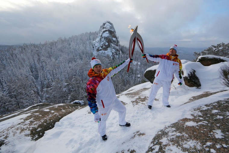 A handout picture taken during the Sochi 2014 Winter Olympic torch relay on November 26, 2013, and released by the Sochi 2014 Winter Olympics Organizing Committee shows Russian mountain-climbers (L-R) Vladimir Gunko and Iliya Efremov 'kissing' with their torches to pass the Olympic flame while standing atop of a rock at the Stolby (Pillars) national nature reserve in the Siberian Krasnoyarsk region, some 3500 km (2174 miles) east of Moscow. Russian torchbearers has started in October the history's longest Olympic torch relay ahead of Winter Games in Sochi, which will take the flame across the country through all 83 of its regions, including extreme locales such as Chukotka, the remote region in Russia's Far East, the turbulent North Caucasus, and even Russia's European exclave Kaliningrad. (Sochi 2014/Getty Images)