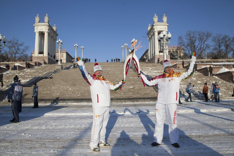 Torchbearers Mikhail Malyuga (L) and Alexander Zaldostanov hold Olympic torches during the Sochi 2014 Winter Olympics torch relay in Volgograd January 20, 2014. (Sochi 2014/REUTERS)