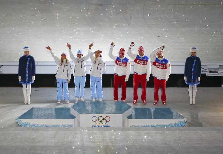 Norway's second-placed Therese Johaug, winner Marit Bjoergen and third-placed Kristin Stoermer Steira, finalists of women's cross-country 30km freestyle and Russia's second placed Maxim Vylegzhanin, winner Alexander Legkov and third placed Ilia Chernousov, finalists of the men's cross-country 50km event attend victory ceremony during the closing ceremony for the 2014 Sochi Winter Olympics (REUTERS/Eric Gaillard)
