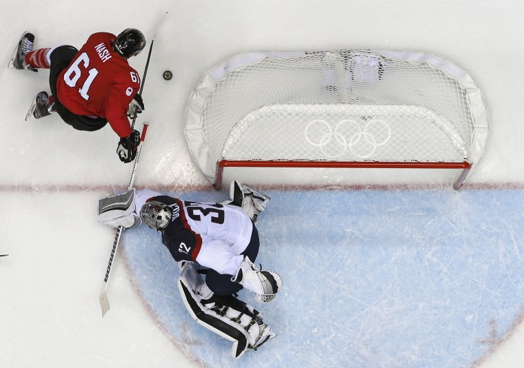 Canada's Rick Nash (L) tries a wrap-around behind Team USA's goalie Jonathan Quick during the third period of their men's ice hockey semi-final game at the Sochi 2014 Winter Olympic Games February 21, 2014. (REUTERS/Jim Young)