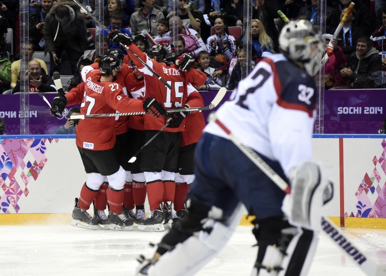 Canada forward Jamie Benn (22) is congratulated by teammates after scoring a goal past USA goalie Jonathan Quick (32) in the second period in the men's ice hockey semifinals during the Sochi 2014 Olympic Winter Games at Bolshoy Ice Dome. (Scott Rovak-USA TODAY Sports)