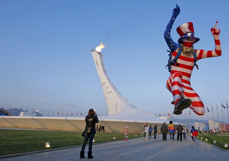 A fan of the U.S. jumps as the Olympic cauldron is seen in the background at the Olympic Park during the 2014 Sochi Winter Olympics, February 21, 2014. (REUTERS/Eric Gaillard)