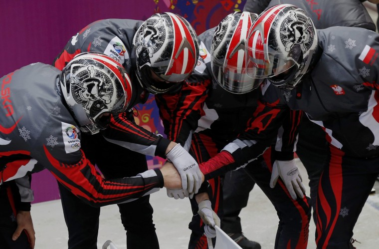 Poland's pilot Dawid Kupczyk (R) and his teammates link hands ahead of a run during a four-man bobsleigh training session at the Sanki Sliding Center in Rosa Khutor, during the Sochi 2014 Winter Olympics February 19, 2014. (REUTERS/Murad Sezer)