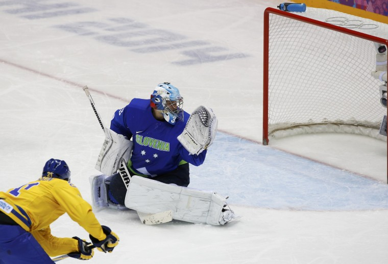 Sweden's Loui Eriksson (L) scores on Slovenia's goalie Robert Kristan during the third period of their men's quarter-finals ice hockey game at the 2014 Sochi Winter Olympic Games, February 19, 2014. (REUTERS/Grigory Dukor)