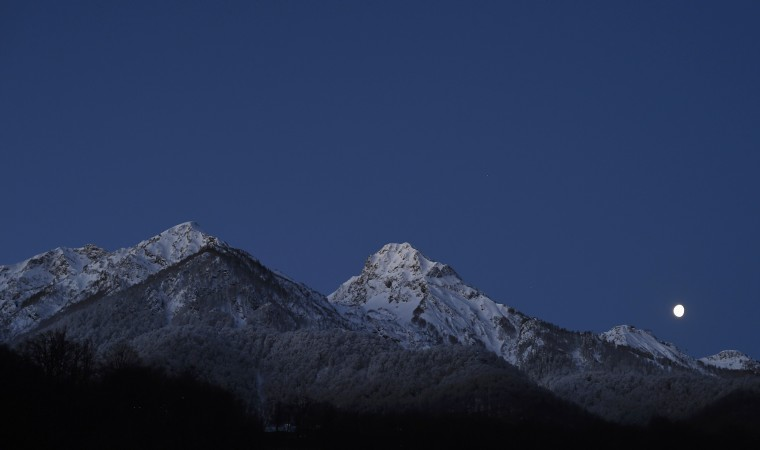 The moon is seen over the mountain ahead of the women's parallel giant slalom competition at the 2014 Sochi Winter Olympic Games in Rosa Khutor February 19, 2014. (REUTERS/Dylan Martinez)