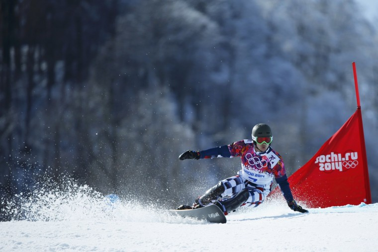 Russia's Vic Wild competes during the men's snowboard parallel giant slalom finals at the 2014 Sochi Winter Olympic Games in Rosa Khutor February 19, 2014. Wild won the Olympic men's snowboard parallel giant slalom gold medal on Wednesday just minutes after his wife Alena Zavarzina had won bronze behind Swiss champion Patrizia Kummer in the women's event. (REUTERS/Mike Blake)