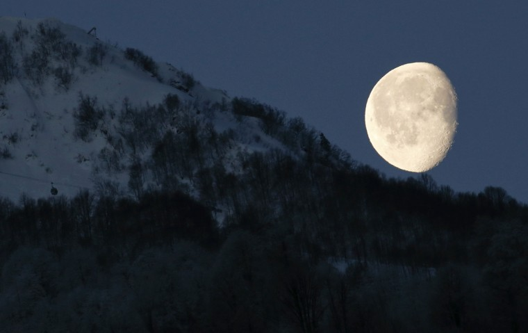 The moon is pictured above the mountains in Rosa Khutor during the 2014 Sochi Winter Olympics February 19, 2014. (REUTERS/Arnd Wiegmann)