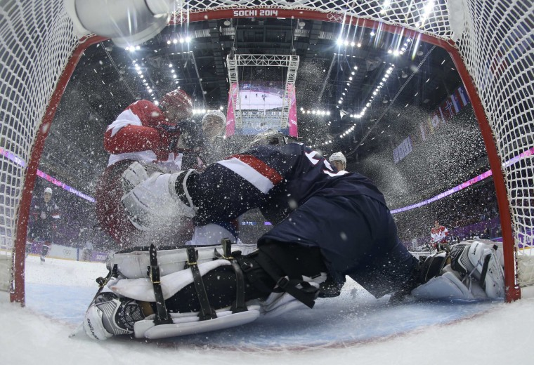Russia's Yevgeni Malkin (L) crashes into Team USA's goalie Jonathan Quick during the first period of their men's preliminary round hockey game at the 2014 Sochi Winter Olympic Games, February 15, 2014. REUTERS/Bruce Bennett/Pool