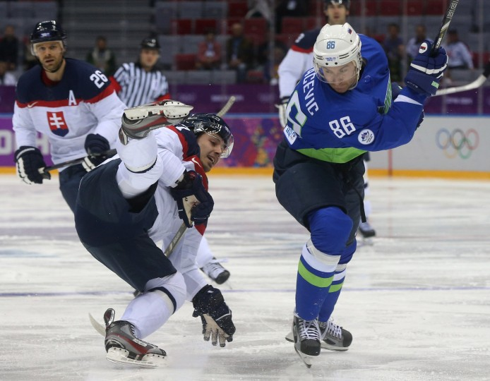 Slovakia forward Tomas Zaborsky (67) falls as Slovenia defenseman Sabahudin Kovacevic (86) moves the puck in the first period of a men's hockey game at Bolshoy Ice Dome during the Winter Olympics in Sochi, Russia, Saturday, Feb. 15, 2014. (Brian Cassella/Chicago Tribune/MCT)