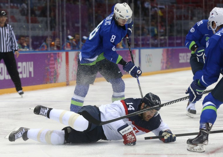 Slovakia defenseman Andrej Meszaros (14) falls in front of Slovenia forward Ziga Jeglic (8) in the first period of a men's hockey game at Bolshoy Ice Dome during the Winter Olympics in Sochi, Russia, Saturday, Feb. 15, 2014. (Brian Cassella/Chicago Tribune/MCT)