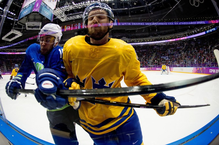 Slovenia forward Ziga Pance (19) and Sweden defensemen Alexander Edler (23) crash into the glass during the first period in a men's hockey quarterfinals game at the Winter Olympics in Sochi, Russia, Wednesday, February 19, 2014. Sweden defeated Slovenia 5-0. (Harry E. Walker/MCT)