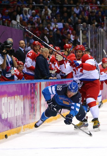 Sami Lepisto #18 of Finland falls to the ice after colliding with Alexander Ovechkin #8 of Russia during the Men's Ice Hockey Quarterfinal Playoff on Day 12 of the 2014 Sochi Winter Olympics at Bolshoy Ice Dome on February 19, 2014 in Sochi, Russia. (Photo by Martin Rose/Getty Images)