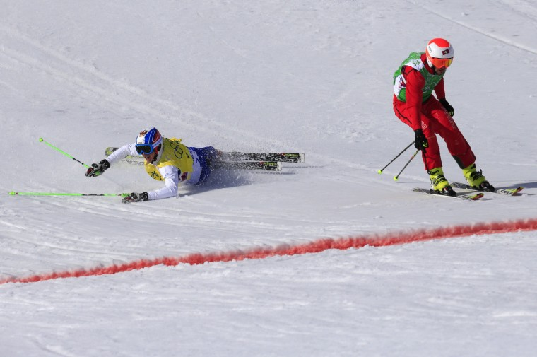 Russia's Egor Korotkov crashes as Switzerland's Armin Niederer crosses the finisk line in the Men's Freestyle Skiing Ski Cross Quarterfinals at the Rosa Khutor Extreme Park during the Sochi Winter Olympics on February 20, 2014. (Alexander Klein/AFP/Getty Images)