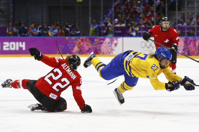 Sweden's Emma Nordin (R) is tripped by Switzerland's Livia Altmann (22) during the second period of their women's ice hockey bronze medal game at the Sochi 2014 Winter Olympic Games February 20, 2014. (REUTERS/Mark Blinch)
